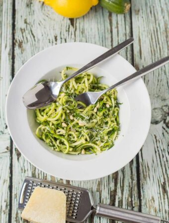 Birds eye view of a bowl of spiralized kale pesto pasta with a fork and spoon in. Two lemons and a courgette at the top and a block of parmesan cheese and grater at the bottom.