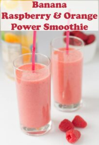Two banana raspberry orange power smoothies side by side with a bottle of orange in the background and raspberries decorated around.