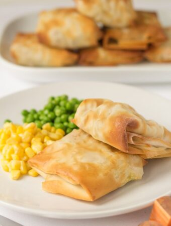 A plate with two chickpea and sweet potato filo parcels served with peas and sweetcorn. Six remaining parcels on a serving platter in the background.
