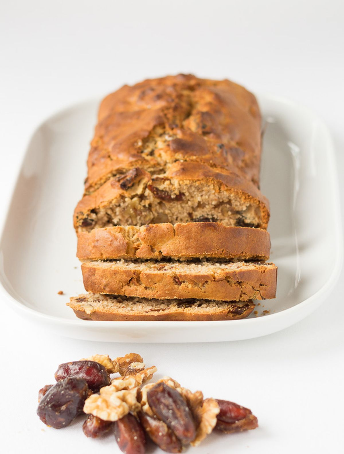 Date and walnut loaf on a white serving platter facing forward with three slices cut off. A pile of date and walnuts in front.