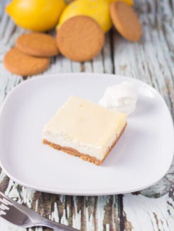 A lemon cheesecake square served on a plate with a fork in front. Biscuits and lemons at the back as decoration.