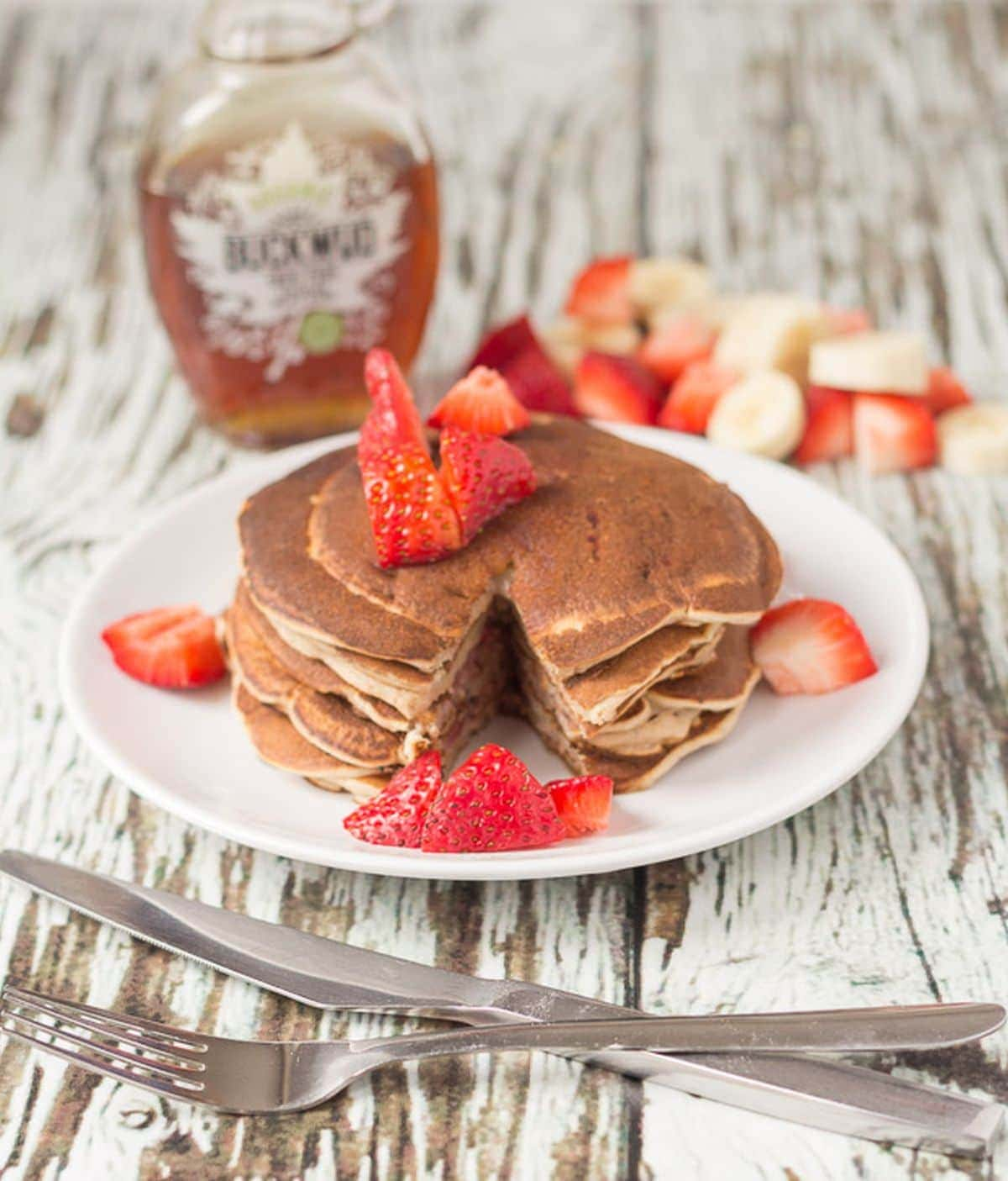 A stack of strawberry banana valentines pancakes on a plate topped with chopped strawberries. Knife and fork to the front. A bottle of maple syrup in the background.
