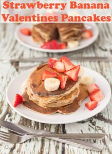 Two plates of strawberry banana valentines pancakes one in front of the other decorated with strawberries and bananas.