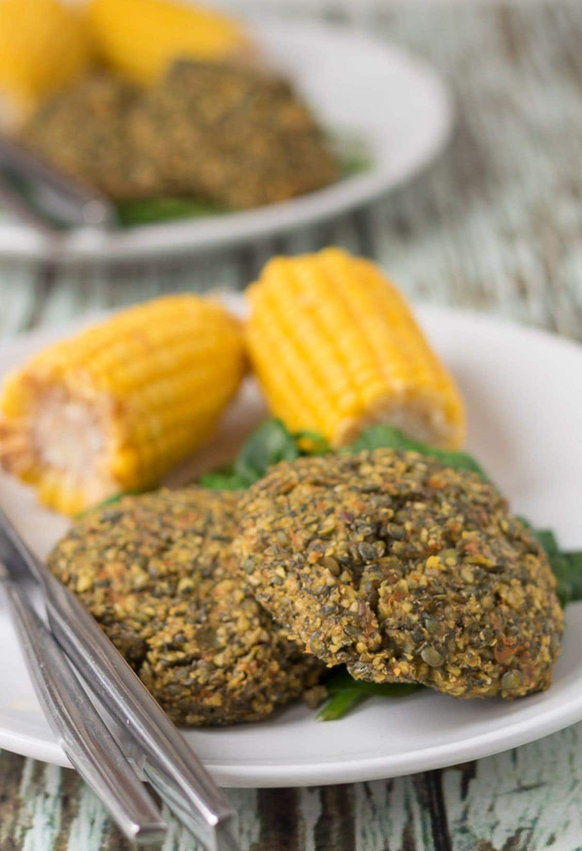 Two oven baked lentil and carrot patties served on a plate with spinach and two corn on the cobs. Another similar plate in the background.