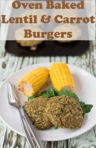 Two oven baked lentil and carrot patties served on a plate with spinach and two corn on the cobs. Pin title text overlay at top.
