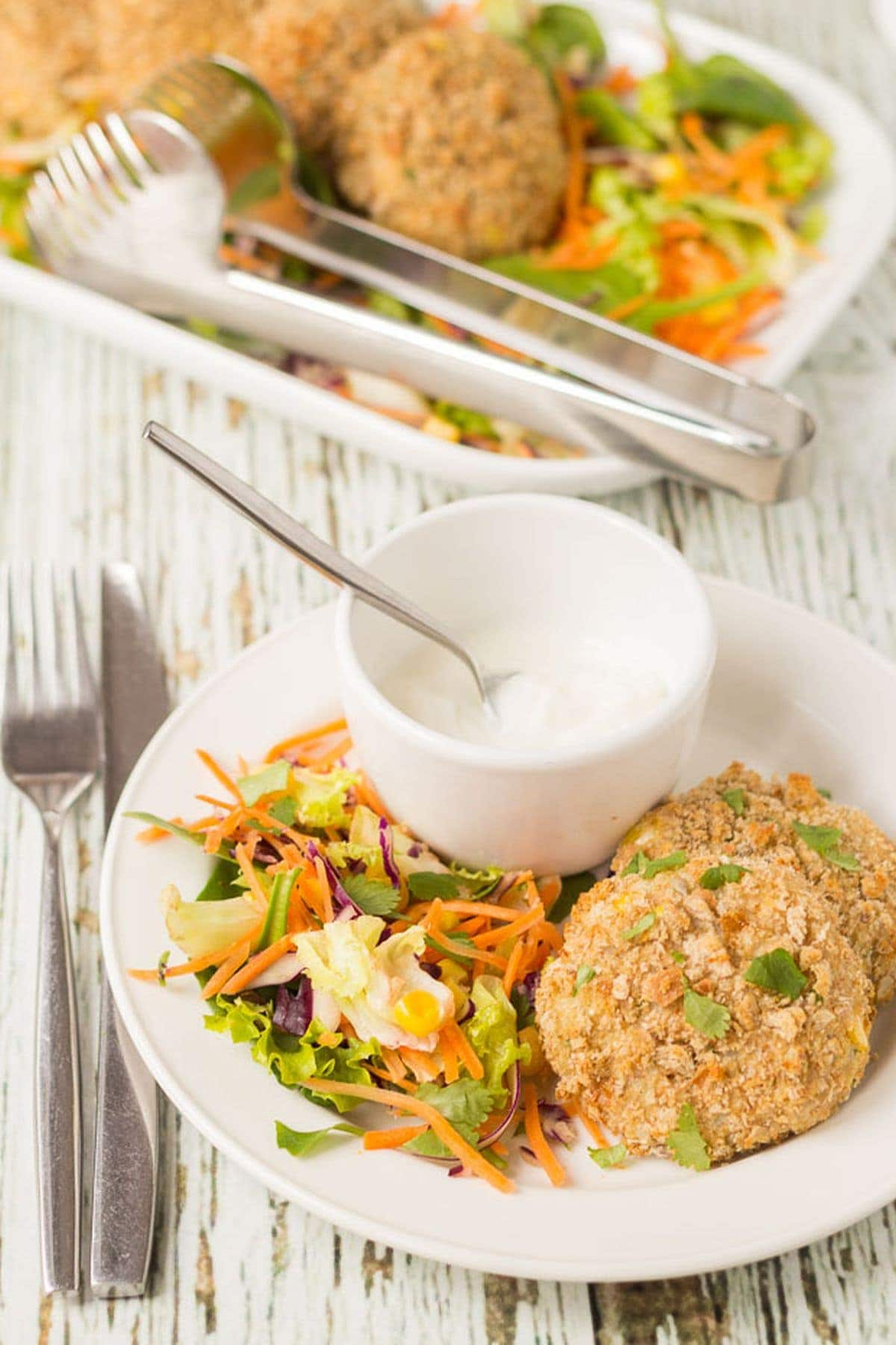 A plate with two oven baked tuna sweetcorn cakes and salad on with a ramekin of mayonnaise. Rest of the cakes in the background on a serving platter with serving tongs on.