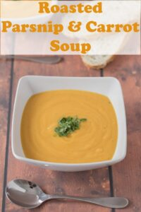 A bowl of roasted parsnip and carrot soup garnished with chopped coriander. Soup spoon in front. Pin title text overlay at top.