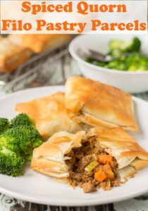 Three spiced quorn filo pastry parcels on a plate with one cut in half and the filling spilling out. Served with broccoli.