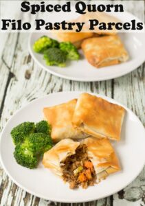 Close up of a plate of three spiced quorn filo pastry parcels served on a plate with broccoli. One parcel cut in half to show filling. Another plate in the background covered over by pin text title overlay.