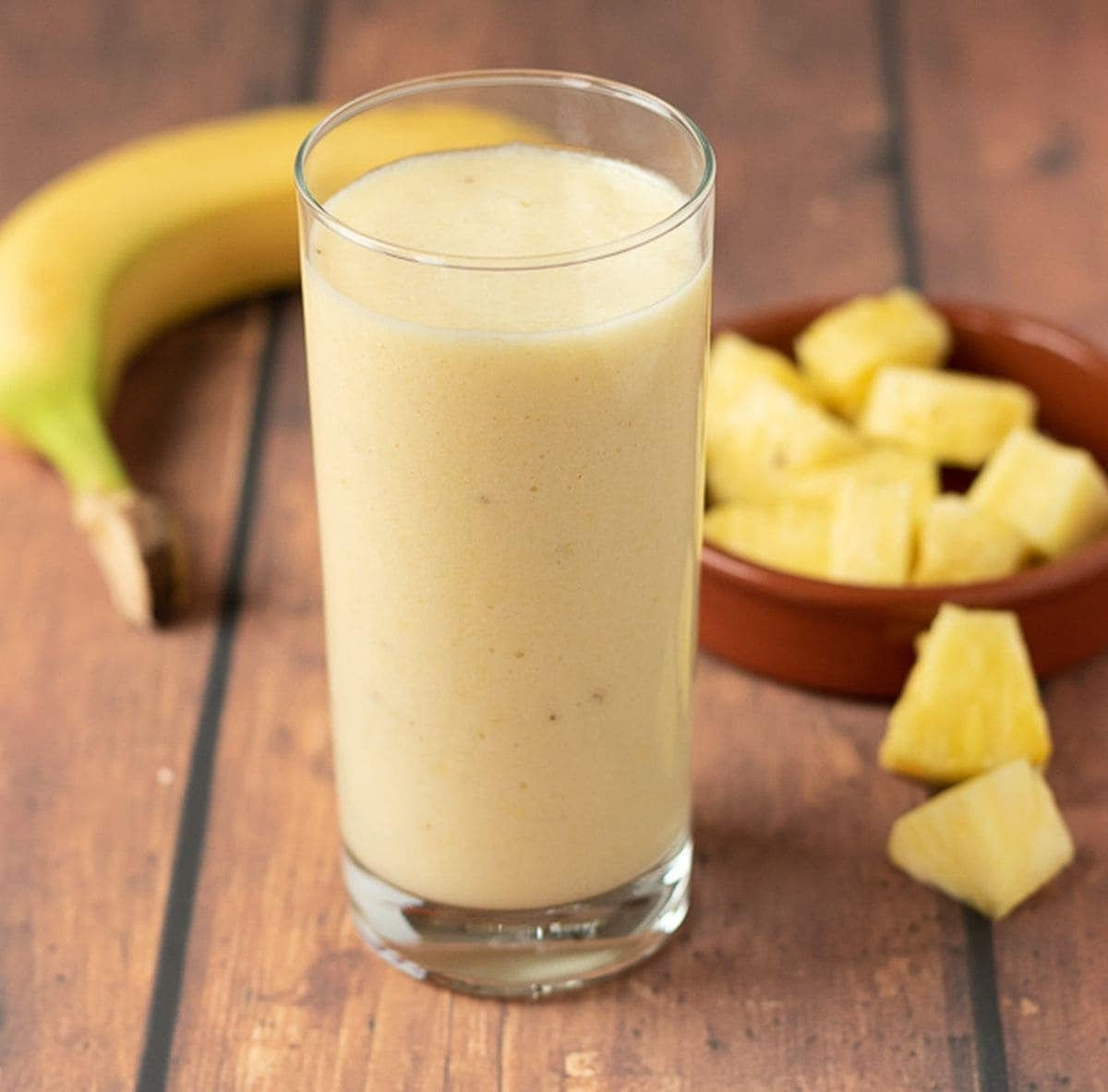 A glass of 4-ingredient tropical banana smoothie. A banana and a dish of pineapple cubes in the background.