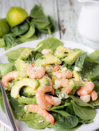 A plate of avocado prawn and coconut salad with a fork to the side. Some spinach leaves and a jug in the background as decoration.