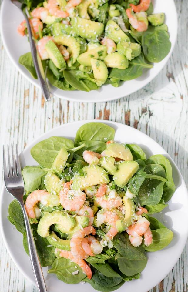 Birds eye view of two plates of avocado prawn and coconut salad with forks to the left side.