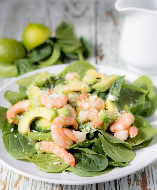 Close up of a plate of avocado prawn and coconut salad. Some spinach leaves, halved limes and a jug in the background as decoration.