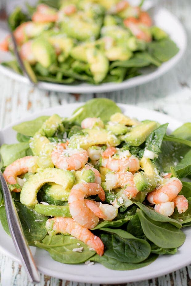Two plates of avocado prawn and coconut salad with forks to the left side.