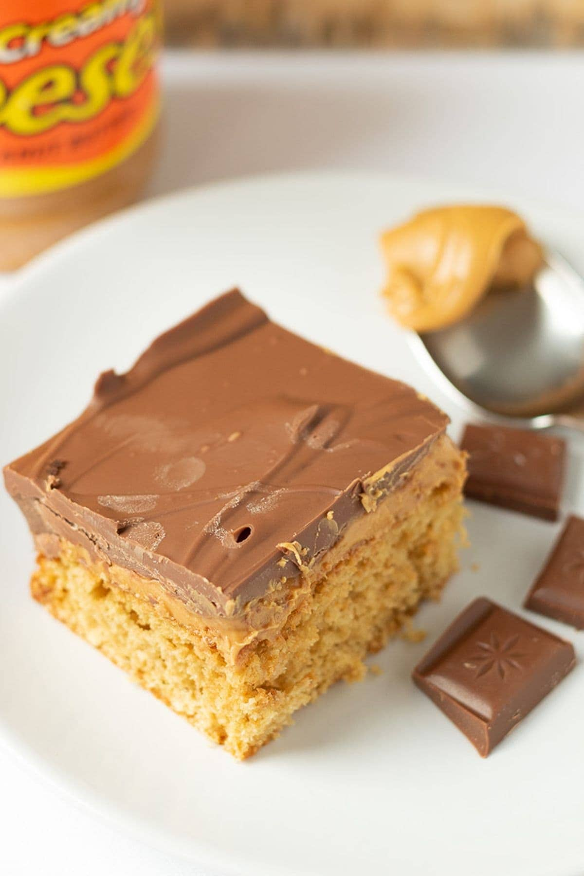 A square of chocolate peanut butter tray bake on a plate surrounded by squares of chocolate and a spoon with peanut butter on. Jar of peanut butter in the background.