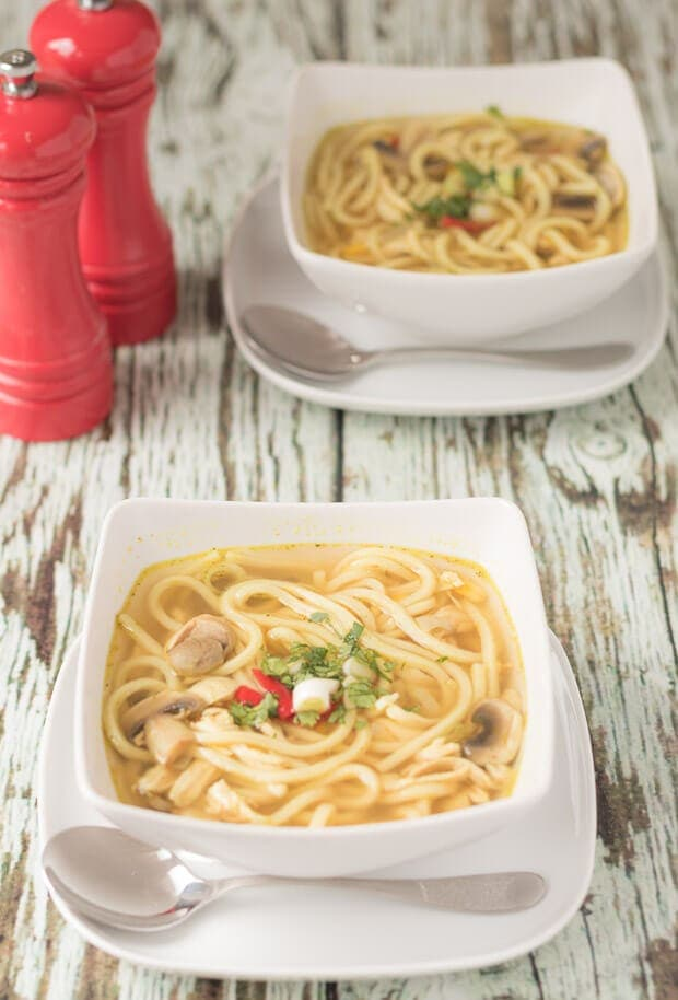 Two square bowls of flu busting spicy chicken noodle soup one in front of the other sitting on a square plates with soup spoons in front. Salt and pepper cellars at the back left.