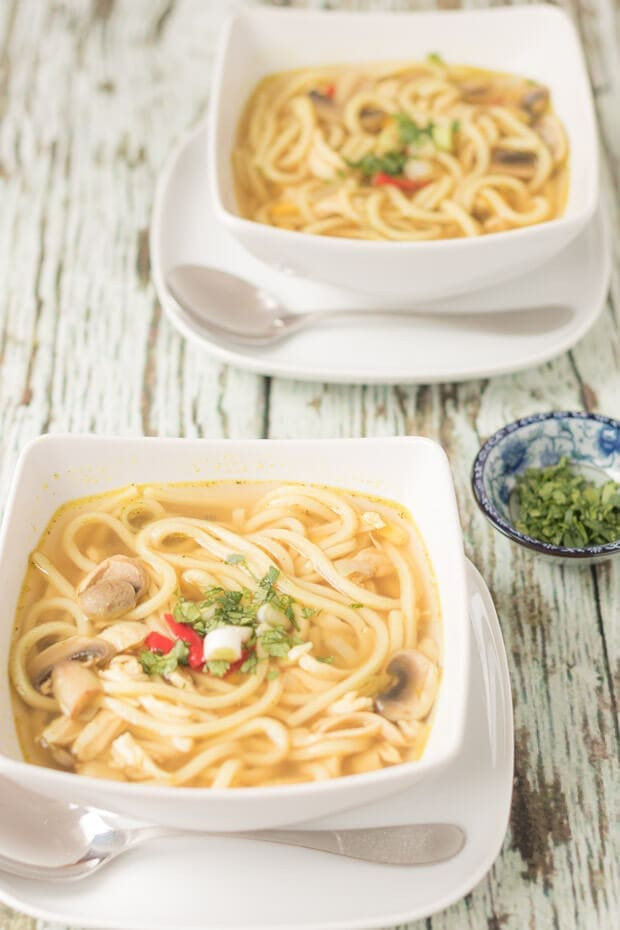 Two square bowls of flu busting spicy chicken noodle soup one in front of the other sitting on a square plates with soup spoons in front. A dish of chopped parsley as garnish to the right side.
