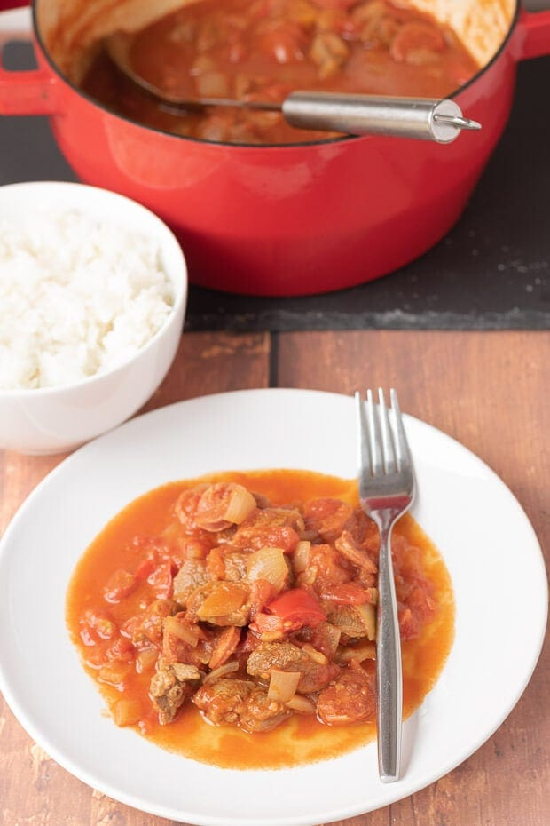 A plate with one pot chorizo and lamb stew served on it and a fork to the side. Rest of casserole pot in the background with a bowl of rice in between.