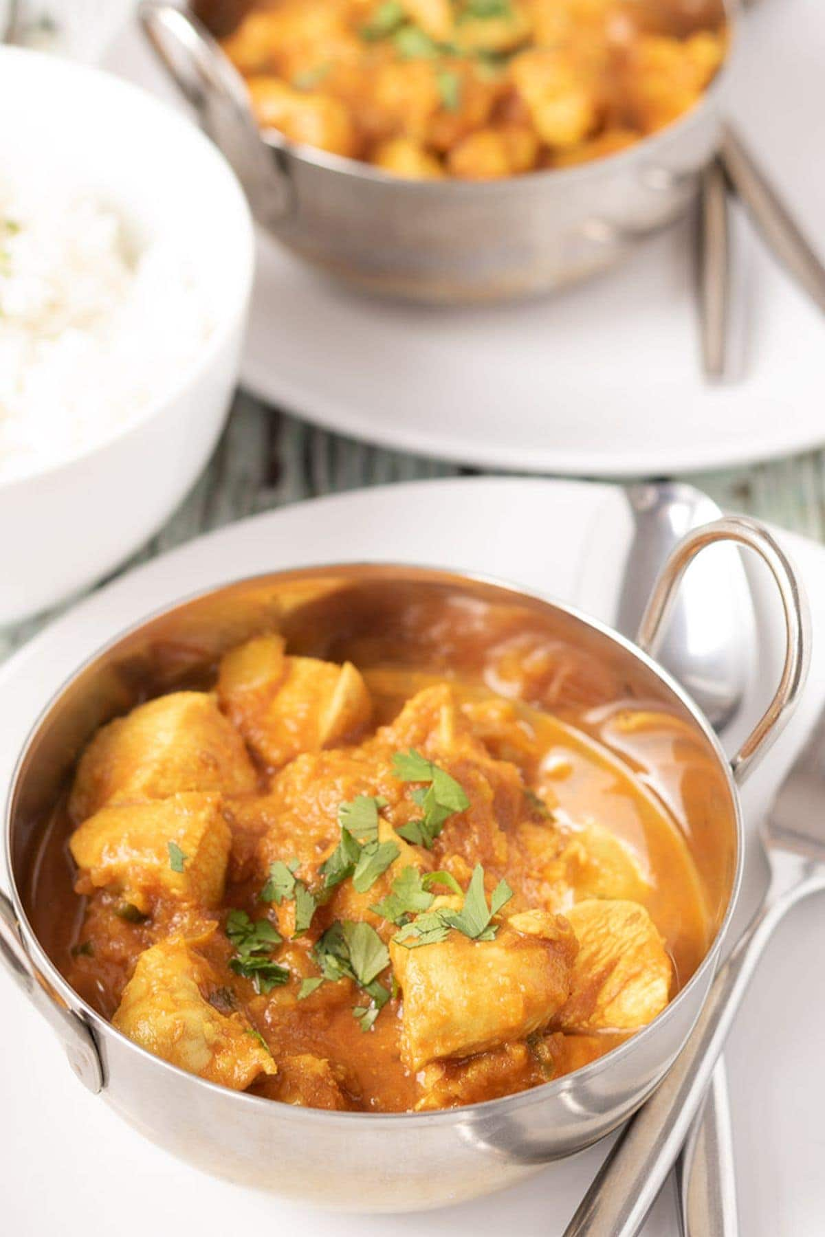 Two balti dishes sitting on plates served with chicken sharabi curry in. Knife and fork to the side and bowl of rice in between.