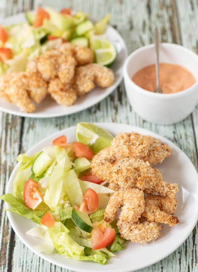 Two plates of healthy baked coconut prawns served with salad and a lime wedge. Dipping sauce in between.