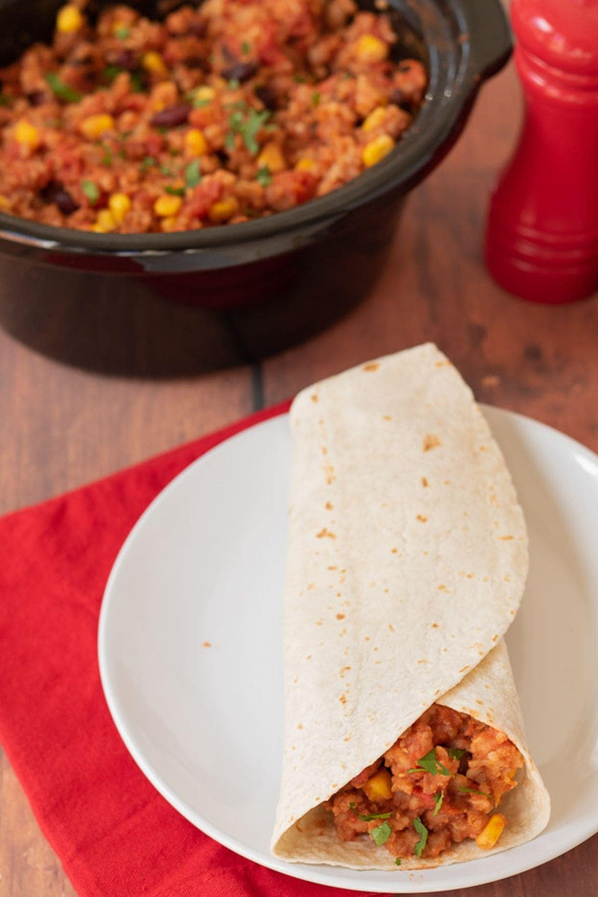 A slow cooker budget bean burrito on a plate. Slow cooker in the background with the rest of the recipe in. Salt cellar to the back right.