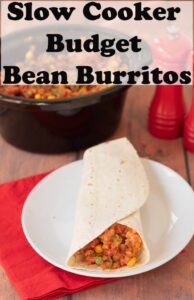A slow cooker budget bean burrito on a plate in front of the slow cooker containing the rest of the budget bean burritos.