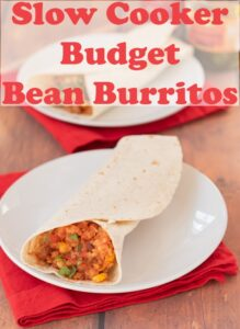 Two plates with slow cooker budget bean burritos on. Red napkins underneath. Pin title text overlay at top.