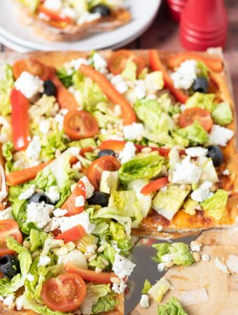 Spring salad filo tart on a chopping board with a square cut from bottom right corner. Plate with the square on in the background and salt and pepper cellars to the right.