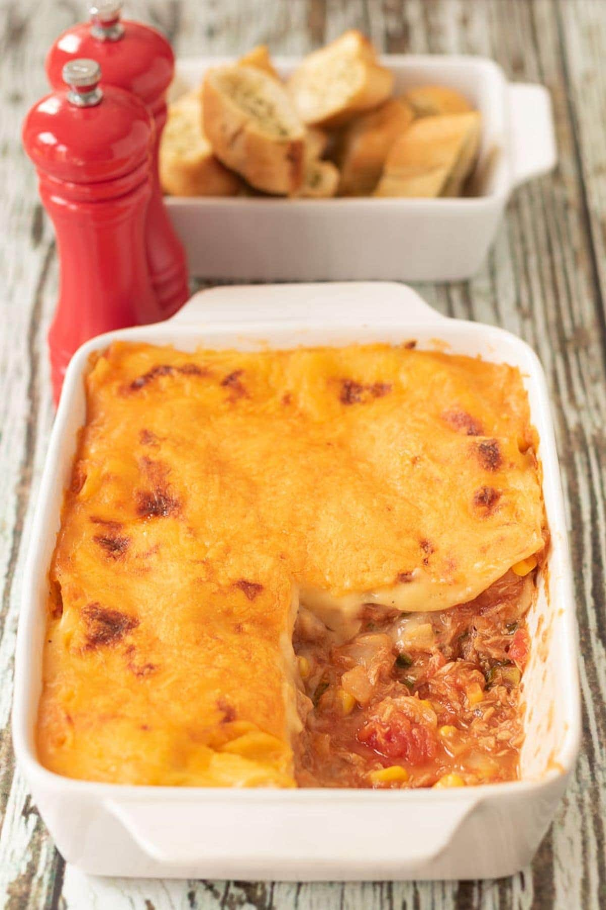 A casserole dish of tuna sweetcorn lasagne with a portion removed. Salt and pepper cellars and a bowl of garlic bread in the background.
