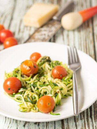 A plate of courgette spaghetti with tomatoes and homemade pesto. Cherry tomatoes, a block of cheese, grater and pestle in the background.