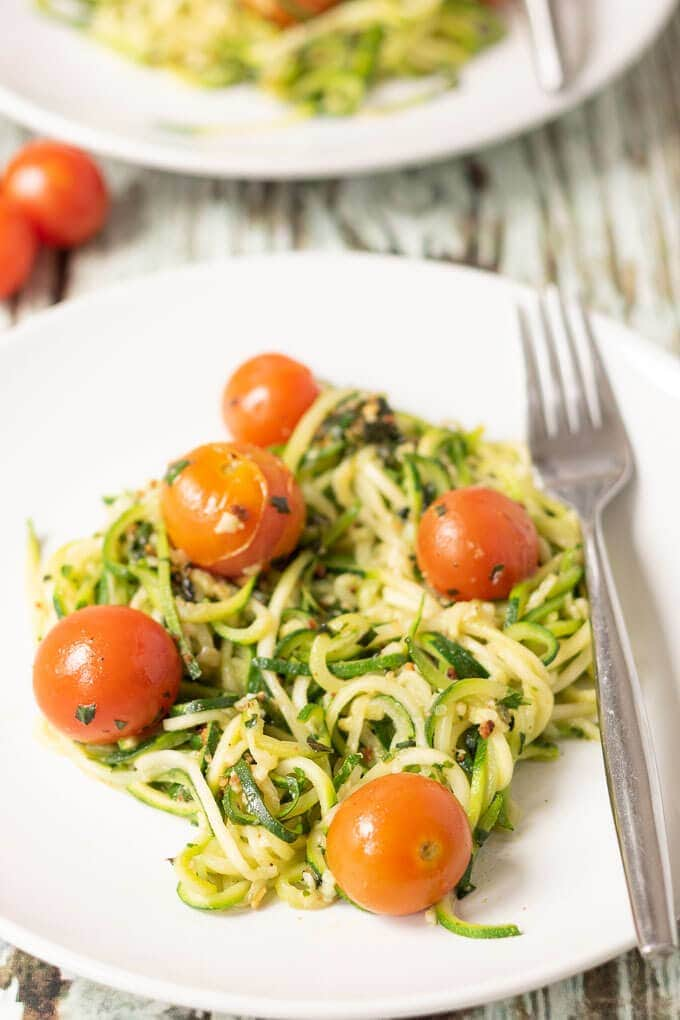 Close up of a plate of courgette spaghetti with tomatoes and homemade pesto with a fork to the right hand side.