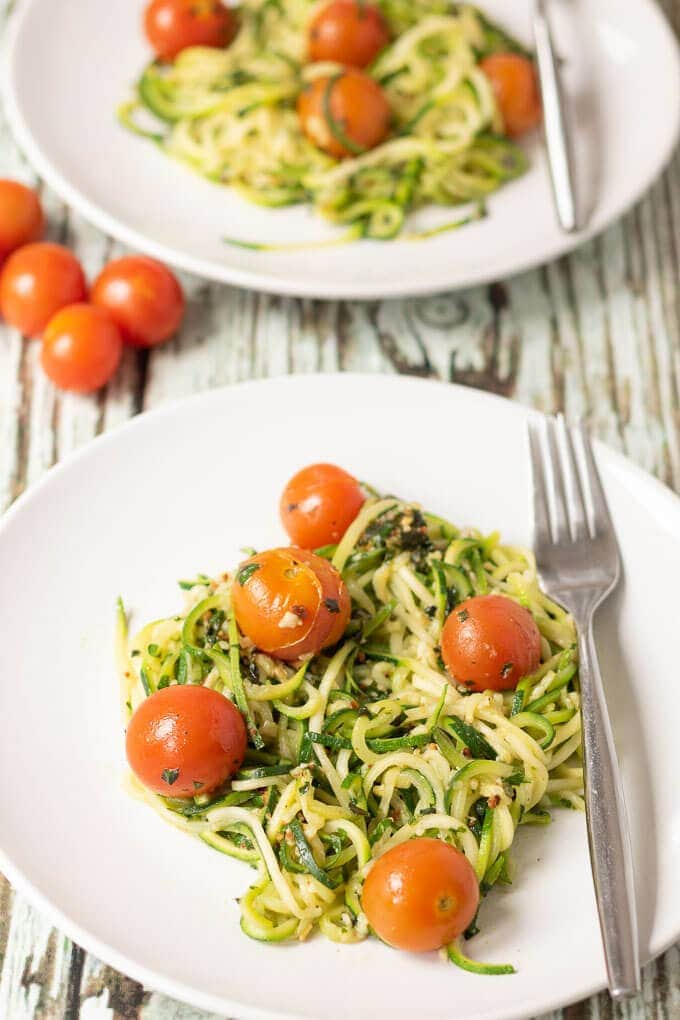 Two plates of courgette spaghetti with tomatoes and homemade pesto. Forks to the right hand side and cherry tomatoes in between.