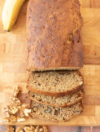 Birds eye view of healthy banana and walnut loaf on a chopping board. Three slices cut off and a banana and walnuts surrounding as decoration.