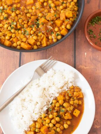Birds eye view of a plate of sweet potato and chickpea curry served with rice and a fork to the side. Rest of the curry in a pan at the top with a dish of garnish to the side.