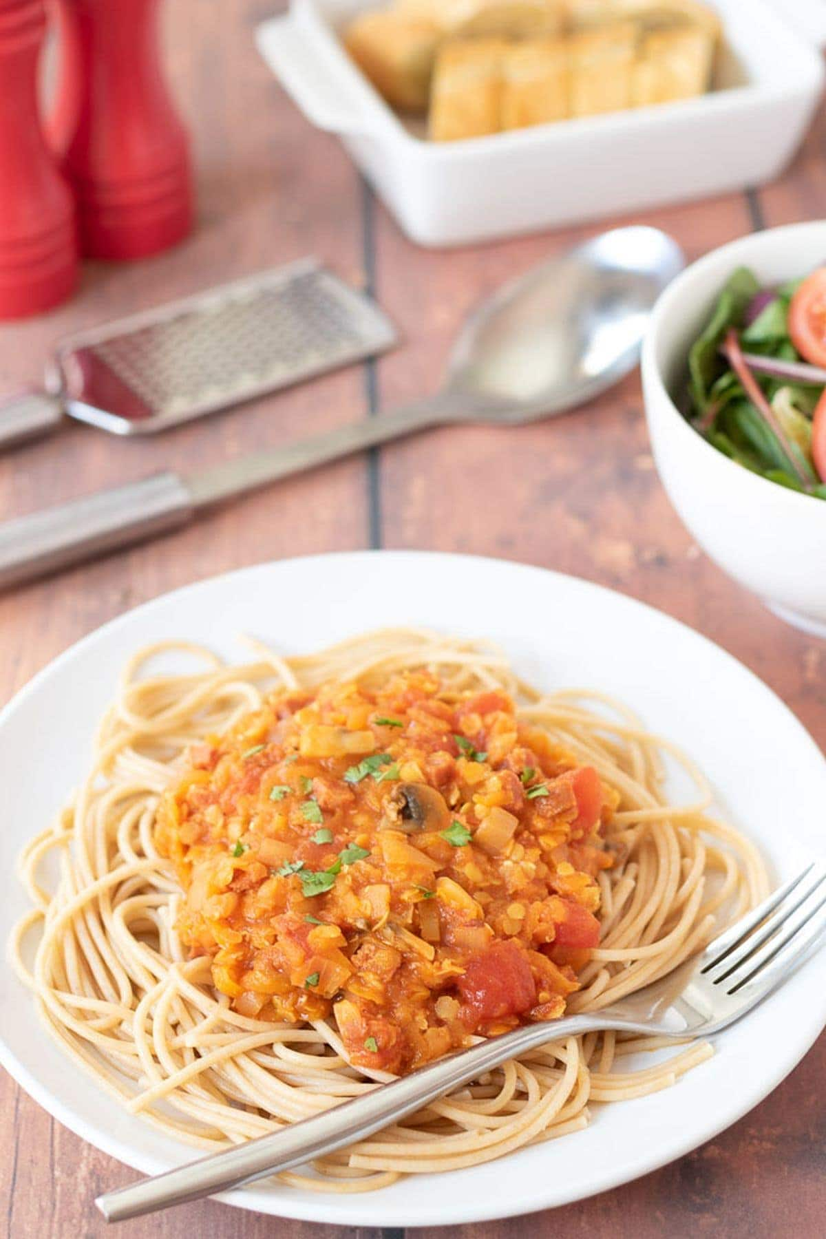 A plate of chorizo lentil bolognese served on a bed of spaghetti. Grater, serving spoon, salt and pepper, garlic bread and a side salad in the background.