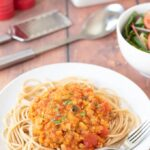 Plate of chorizo bolognese with lentils on top of spaghetti