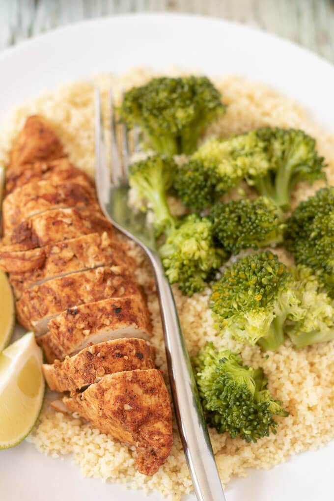Succulent oven baked lime chicken breasts on a plate served with couscous, broccoli and lime wedges