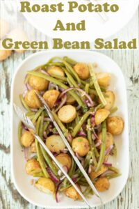 Birds eye view of a serving dish of roast potato and green bean salad with serving tongs on.