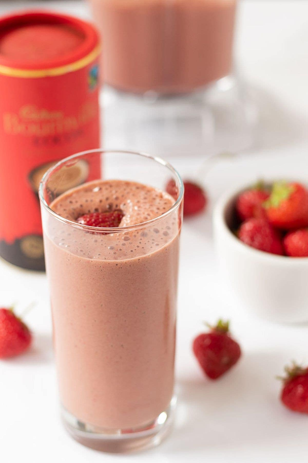 A tall glass of easy chocolate strawberry smoothie. Container of drinking chocolate, a dish of strawberries to the side and the rest of the smoothie in a blender jug in the background.