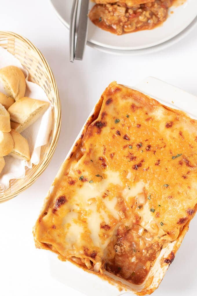 Birds eye view of easy Quorn lasagne cooked on table served with a slice taken out and a serving of garlic bread.