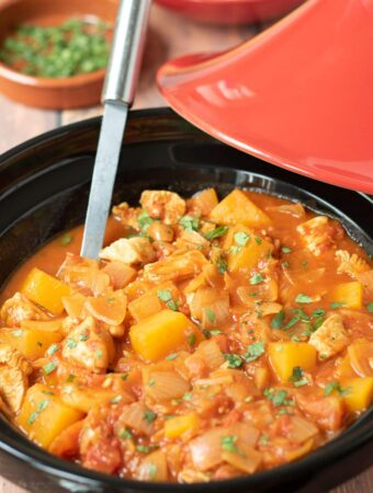 Easy Moroccan chicken tagine with a serving spoon in. A dish of garnish and bowl of couscous in the background.