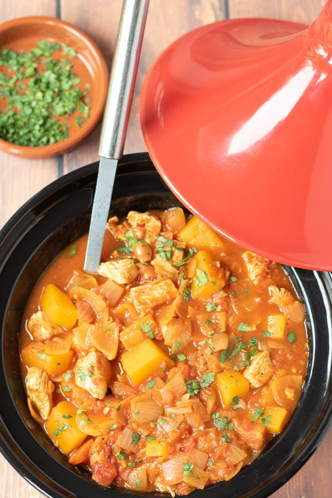 Birds eye view of Moroccan chicken tagine dinner cooked in tagine dish ready to serve with dish of chopped coriander.