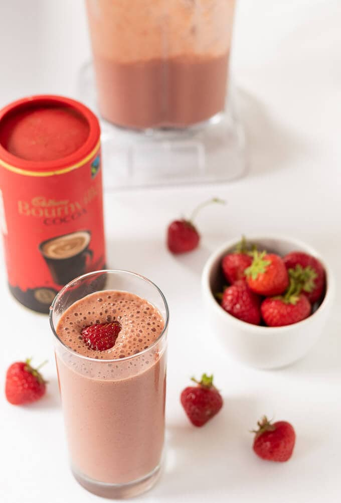 Easy chocolate strawberry smoothie in a tall glass ready to drink with a bowl of strawberries and cocoa powder container in the picture.