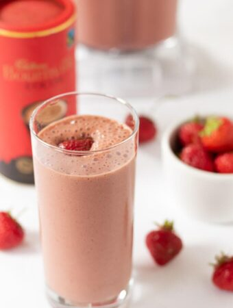 Healthy chocolate strawberry smoothie in a tall glass garnished with a strawberry ready to drink!