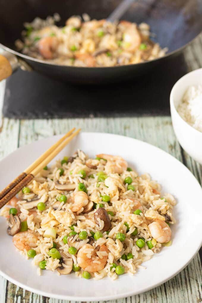 Leftover rice prawn and mushroom stir fry on a plate in front of a wok,