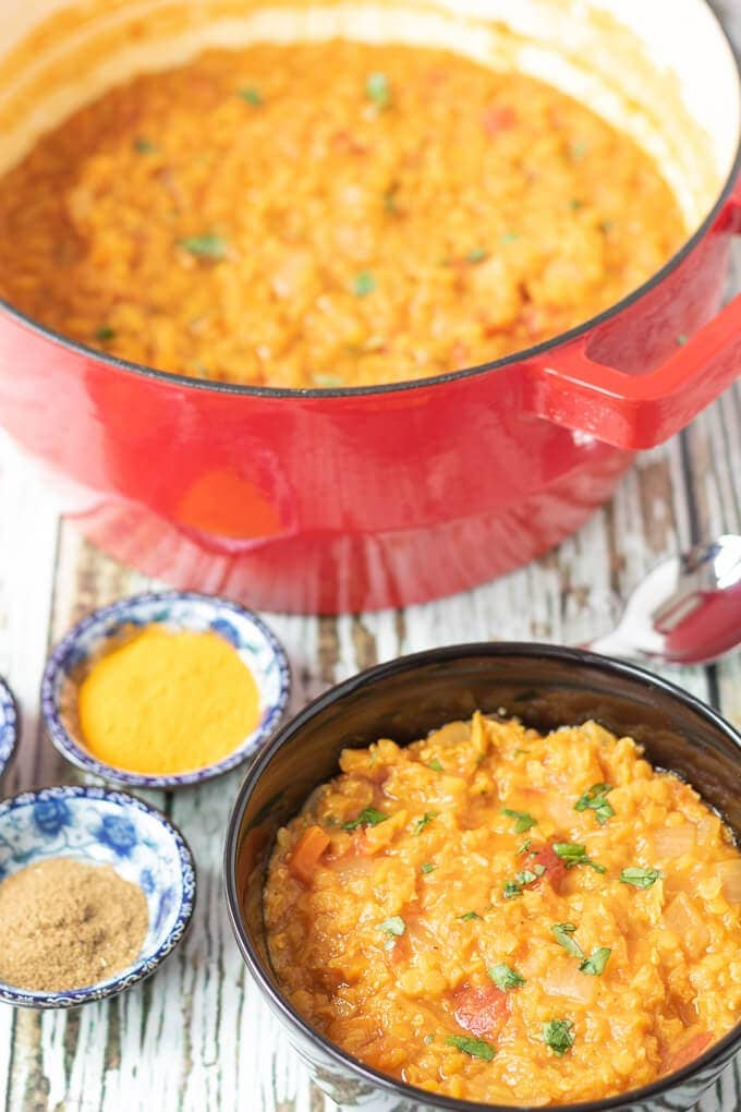 Moroccan Lentil soup served from red casserole pot into back serving dish ready to eat.