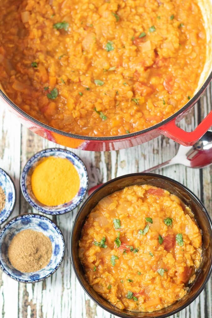 Birds eye view of Moroccan lentil soup in casserole pot and served in a smaller dish at the front.