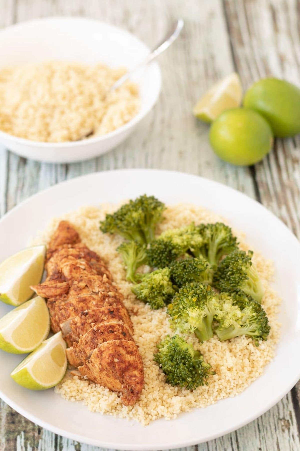 A plate with oven baked lime chicken served on a bed of rice and broccoli with lime wedges beside. A bowl of rice and two and a half limes in the background.
