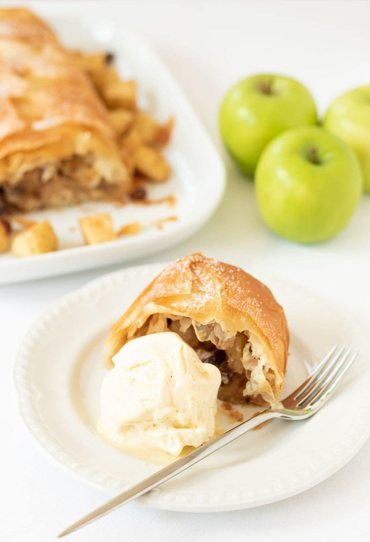 Sugar free easy apple strudel served on a plate with a blob of ice cream and a fork beside. Rest of the strudel and three apples in the background.
