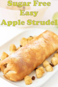 Sugar free easy apple strudel laid on a white serving dish decorated with a border of chopped apples and sultanas.